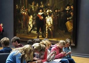 """Adolescentes mergulhados no celular de costas para """"Ronda Noturna"""" de Rembrandt em museu em Amsterdã"""